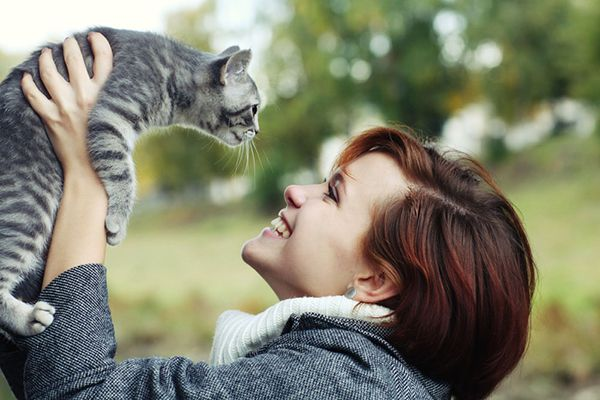 A happy woman holding a cat in the air.