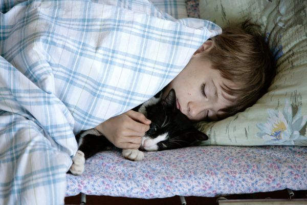 A woman cuddles a black and white cat in her sleep.