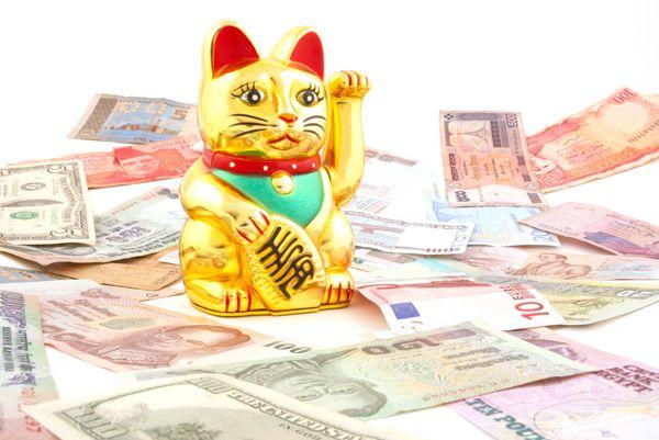 A Maneki Neko, or lucky cat, surrounded by money.