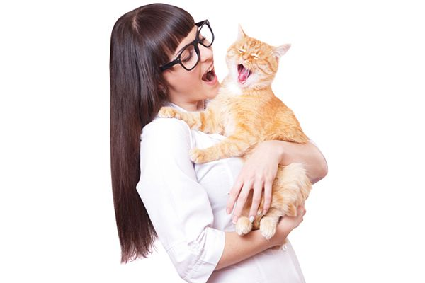 A woman in glasses singing to her ginger cat.