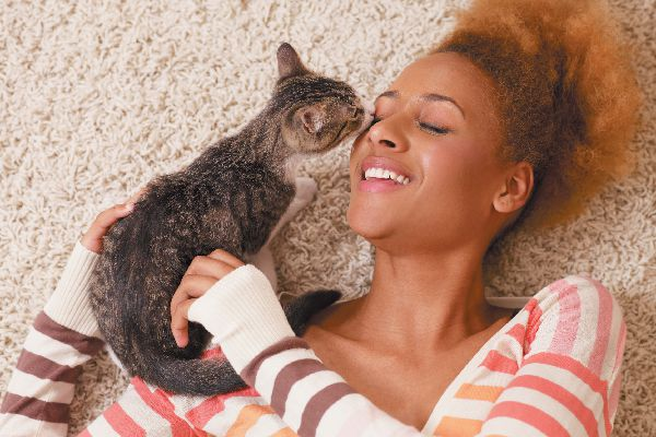 A woman kissing a cat or kitten on the floor.