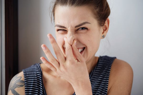 A woman holding her nose like it smells.